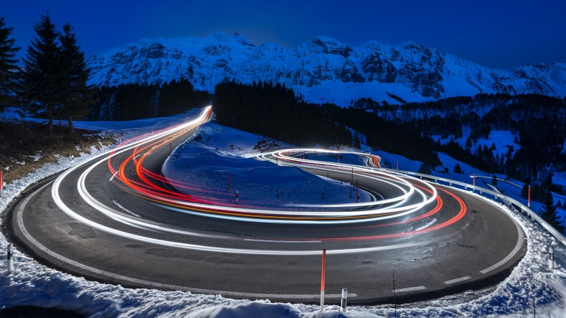Photography Of Curved Lighting Road Surrounded Snow Covered Mountains 4K 5K HD Wallpaper