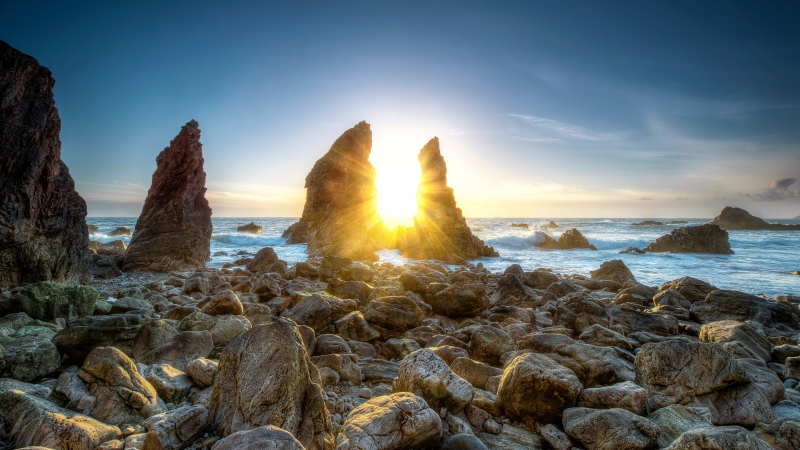 Sunlight Passing Through Rocks Between Seashore Under Blue Sky During Daytime 4K 5K HD Nature Wallpaper