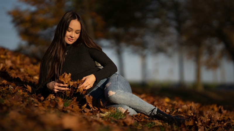 Girl Model Is Sitting On Dry Leaves Wearing Black Top And Blue Jeans 4K 5K HD Girls Wallpaper