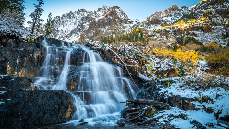 Beautiful Waterfall On Rocks With Landscape View Of Snow And Yellow Flowers Covered Mountains Under Blue Sky 4K 5K HD Nature Wallpaper